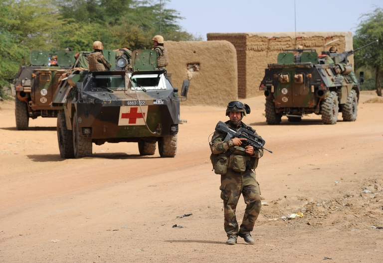 <p>French soldiers patrol at the site where a suicide bomber blew himself up on February 10, 2013 in northern Gao on the road to Gourem.</p>