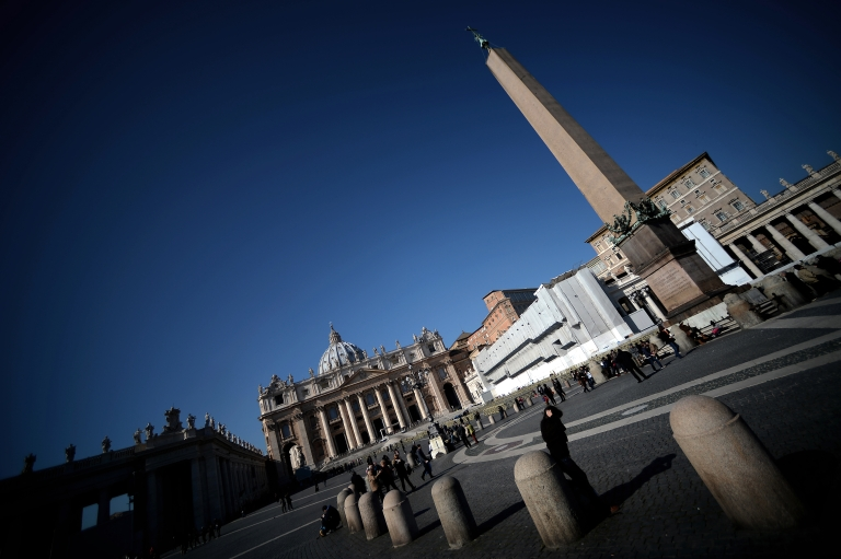 <p>People walk in St. Peter's Square in front of the St. Peter's Basilica on February 19, 2013 at the Vatican City. Pope Benedict XVI will be hosted in the convent of Mater Ecclesiae (Mother of the Church) offering him a substantial four-story modern home complete with contemporary chapel, garden and a roof terrace looking out from a rise dominated by the Holy See's TV transmission tower. Pope Benedict XVI began a week-long spiritual retreat out of the public eye on Monday ahead of his resignation on February 28 with the field of candidates to succeed him still wide open.</p>