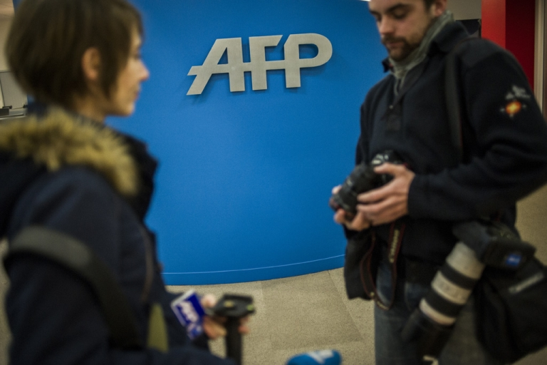 <p>Journalists arrive at the Agence France Presse headquarters in Paris on January 4, 2013.</p>