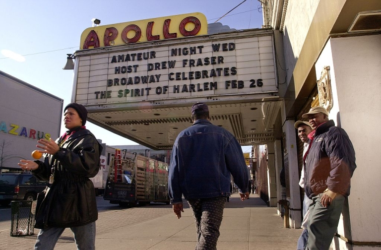 <p>Pedestrians walk by the famous Apollo theater on 125th Street in Harlem, New York. (Photo by Spencer Platt/Newsmakers)</p>