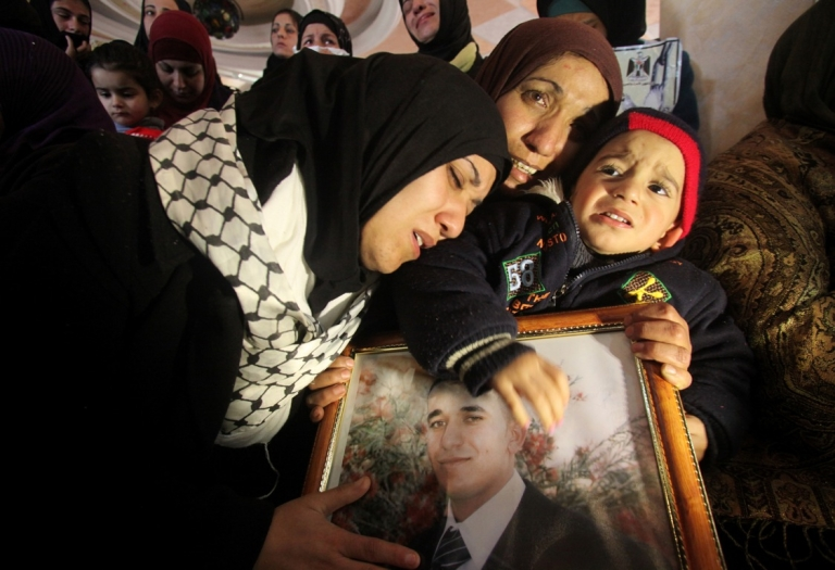 <p>The sisters of Arafat Jaradat (picture), a Palestinian inmate who died in an Israeli prison, mourn their brother's death while embracing his son Muhannad during his funeral in the West Bank village of Saair on February 25, 2013.</p>