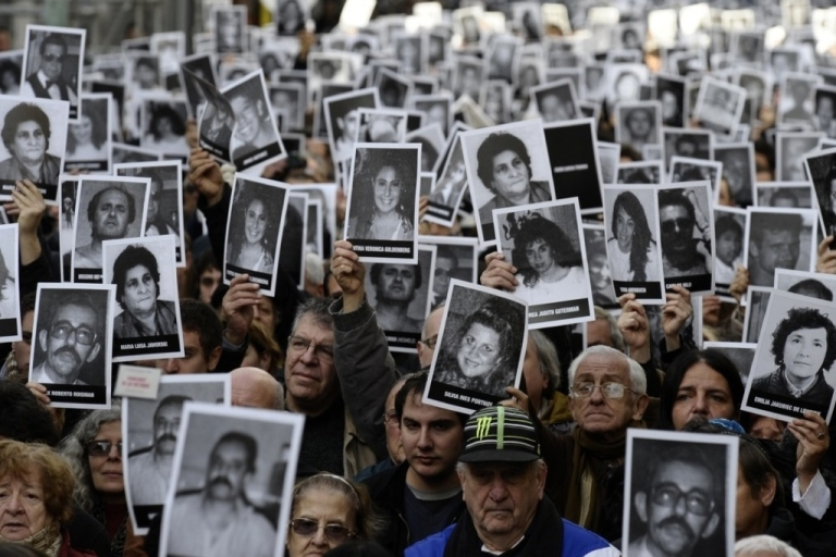 <p>People hold portraits of victims of the terrorist bombing attack against the Argentine-Israeli Mutual Society (AMIA) institute that killed 85 people and injured 300, during the commemoration of its 18th anniversary, in Buenos Aires on July 18, 2012.</p>