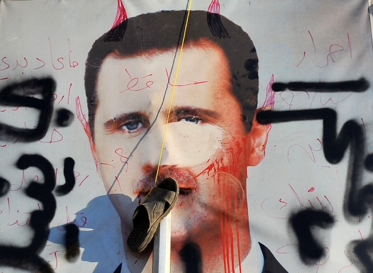 <p>A slipper hangs on a vandalised poster of Syrian President Bashar al-Assad in Aleppo on July 24, 2012.</p>