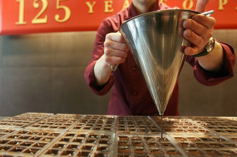 <p>Could this be the chocolate used to flavor Belgian stamps? Here, chocolate maker Denis Vernaillen makes chocolates at a Cote D'or shop in Brussels.( DOMINIQUE FAGET/AFP/Getty Images)</p>