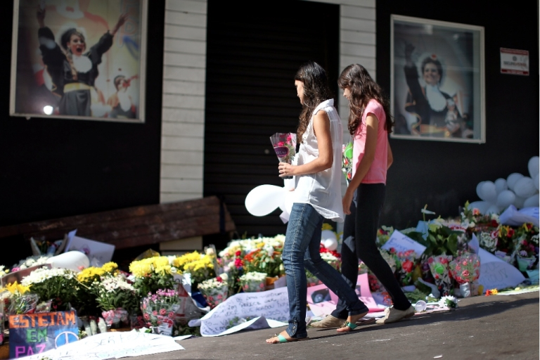 <p>Friends and family lay flowers outside the nightclub in Brazil where more than 230 young people perished in a fire.</p>