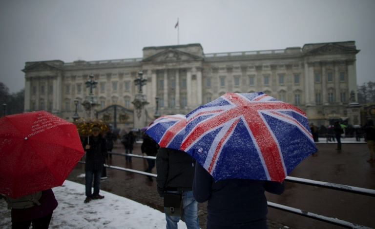 <p>Tourists gather in front of Buckingham Palace during snowfall in central London on January 20, 2013.</p>