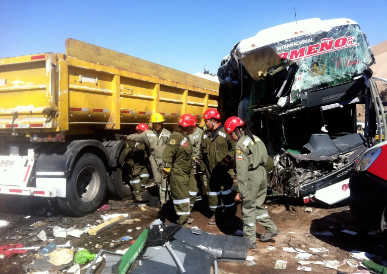 <p>Rescuers work on November 5, 2012 on the wreckage of a bus that collided with a lorry on Route 5 North in Antofagasta, 1400 km north of Santiago killing at least six Peruvian nationals.</p>