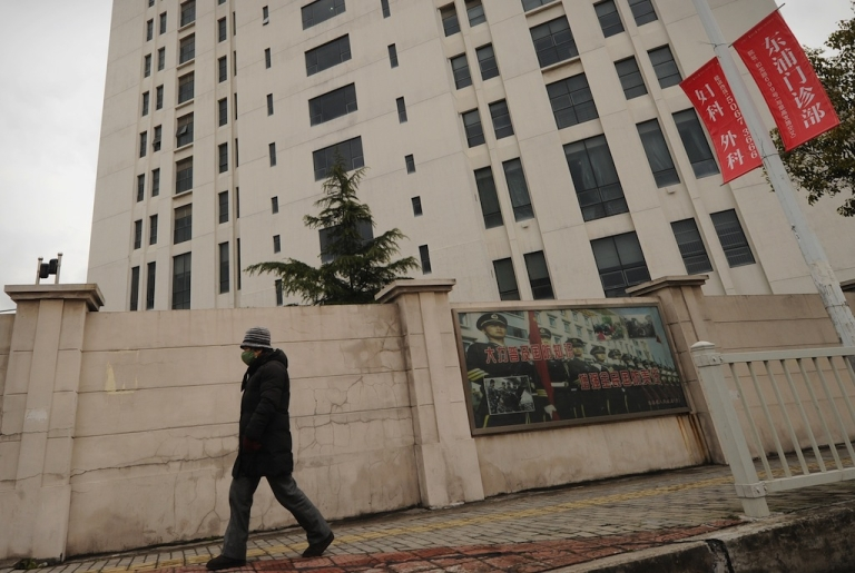 <p>A person walks past a 12-story building alleged in a report by the Internet security firm Mandiant to be the home of a Chinese military-led hacking group on Feb. 19, 2013.</p>