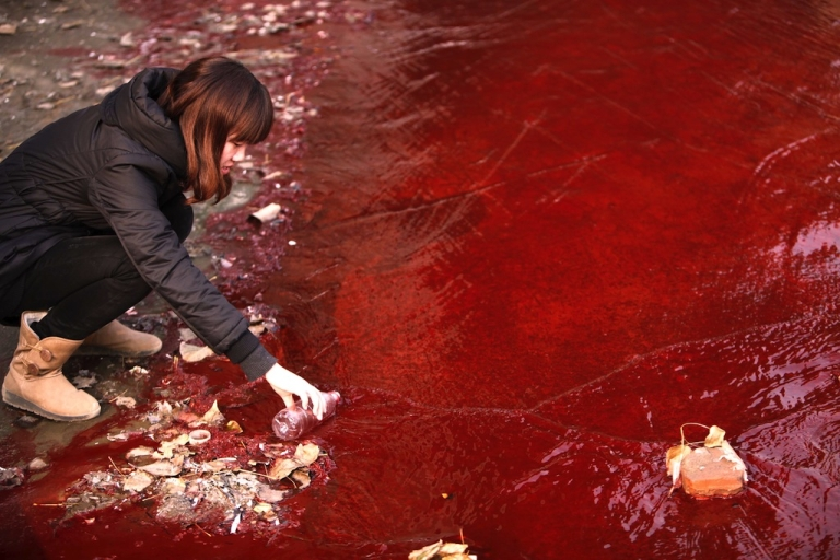 <p>A woman collects a sample of the red polluted water flowing from a sewer into the Jian River in Luoyang, north China's Henan province on Dec. 13, 2011.</p>