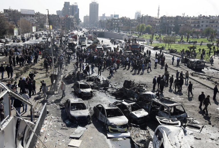 <p>A general view shows burnt cars at the scene of a powerful car bomb explosion near the headquarters of Syria's ruling Baath party in the centre of Damascus on February 21, 2013. The blast sent thick smoke billowing across the capital's skyline, killing dozens of people and causing widespread destruction.</p>