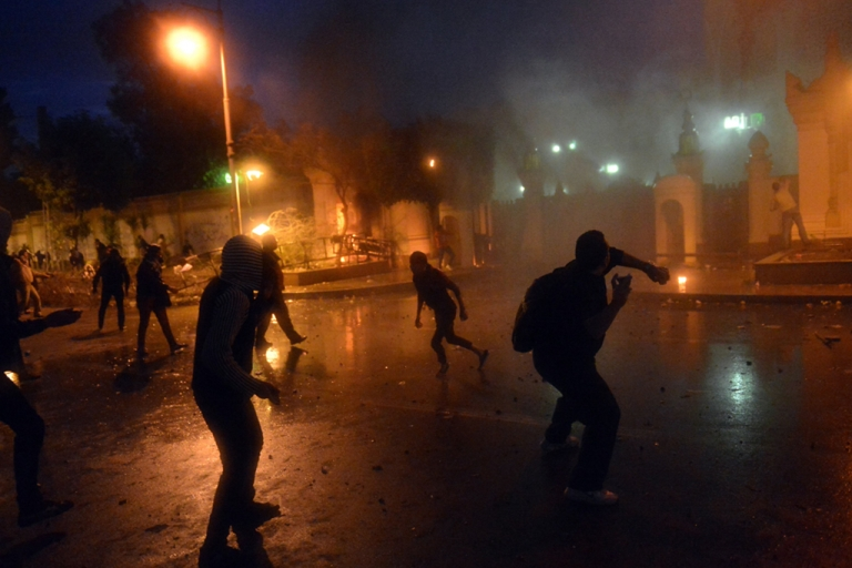 <p>Egyptian protesters throw stones during clashes with riot police in front of the presidential palace in Cairo on Feb. 1, 2013, as thousands of Egyptians flooded the streets in a show of opposition to the Islamist President and the Muslim Brotherhood. Egyptian security used water cannon and fired shots into the air as protesters threw petrol bombs and stones into the grounds of the presidential palace.</p>