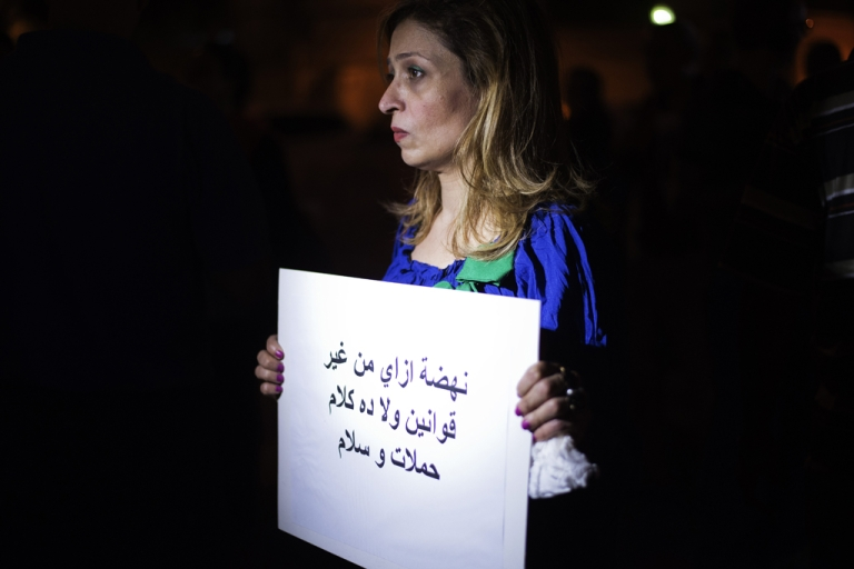 <p>An Egyptian woman holds a slogan which reads in Arabic