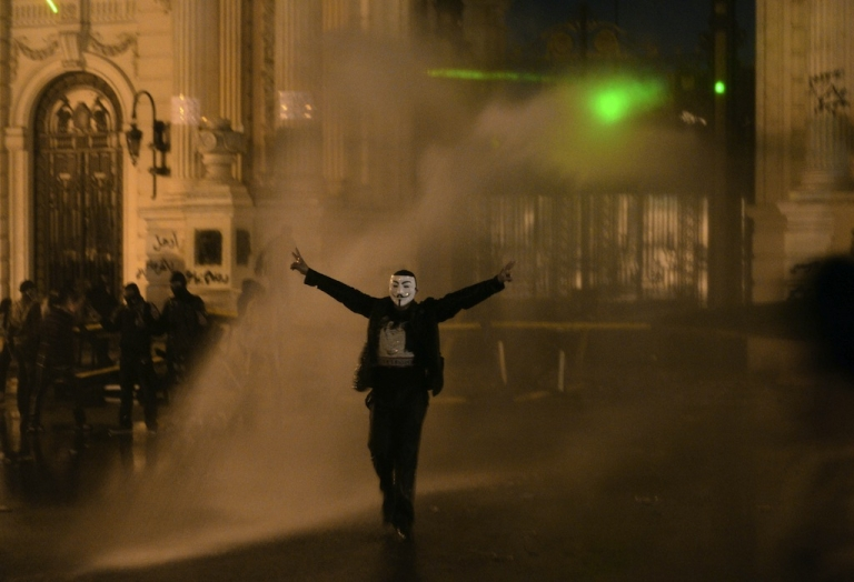 <p>A protestor wearing a Guy Fawkes mask is sprayed as Egyptian security use water cannons to disperse anti-government protestors throwing stones into the grounds of the al-Kobaa Presidential palace in Cairo, on Feb. 15, 2013.</p>