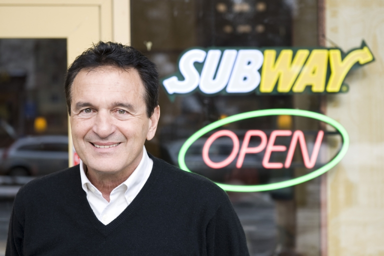 <p>Fred DeLuca, president and founder of sandwich maker Subway, poses during an interview in front of a Subway restaurant at