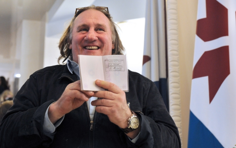 <p>French actor Gerard Depardieu (C) holds his passport registration at the theatre in Saransk, Russia on February 23, 2013. Depardieu, who was granted a Russian passport by President Vladimir Putin after complaining about high tax rates in France.</p>