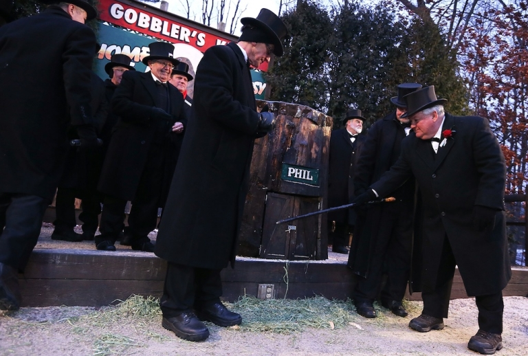 <p>President Bill Deeley (R) of Punxsutawney's 'Inner Circle' tap on the door of Punxsutawney Phil's burrow as he and groundhog co-handlers John Griffiths (2nd R) and Ron Ploucha (3rd L) entice Phil out during the 127th Groundhog Day Celebration at Gobbler's Knob on February 2, 2013 in Punxsutawney, Pennsylvania.</p>