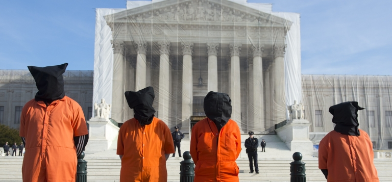 <p>Protesters wear prison jump suits and hoods during an anti-Guantanamo Bay military prison demonstration in front of the US Supreme Court in Washington, DC, on Jan. 8, 2013.</p>