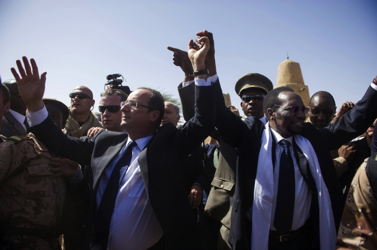 <p>France's President Francois Hollande (L) flanked by Mali's interim president Dioncounda Traore (R), wave as Hollande arrives at the airport of Timbuktu, the second step of his one-day visit in Mali, on February 2, 2013. Islamists had torched the building housing priceless ancient manuscripts as they fled the town.</p>