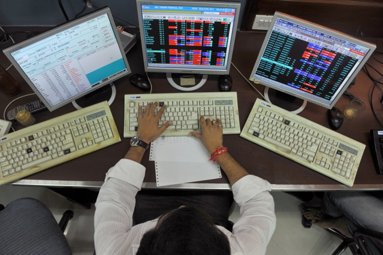<p>A stockbroker monitors share prices during trade at a brokerage house in Mumbai on Aug. 8, 2011.</p>