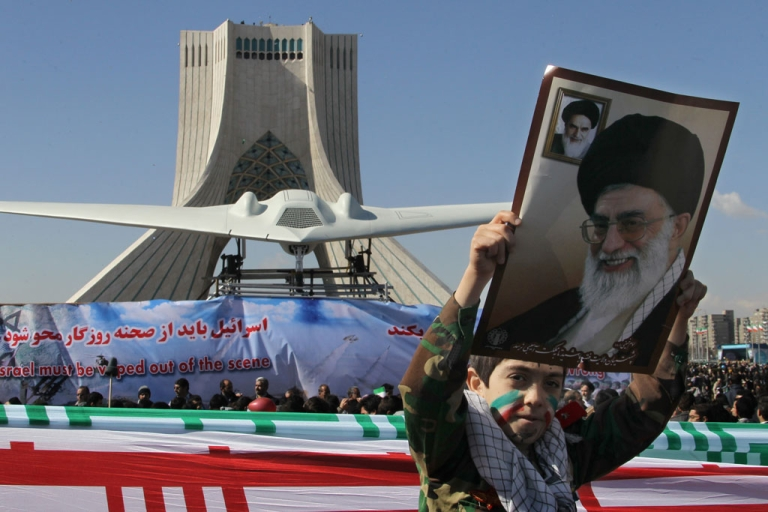 <p>An Iranian boy holds a portrait of supreme leader Ayatollah Ali khamenei as he walks past a replica of the captured US RQ-170 drone on display next to the Azadi (Freedom) tower during the 33rd anniversary of the Islamic revolution in Tehran on February 11, 2012.</p>