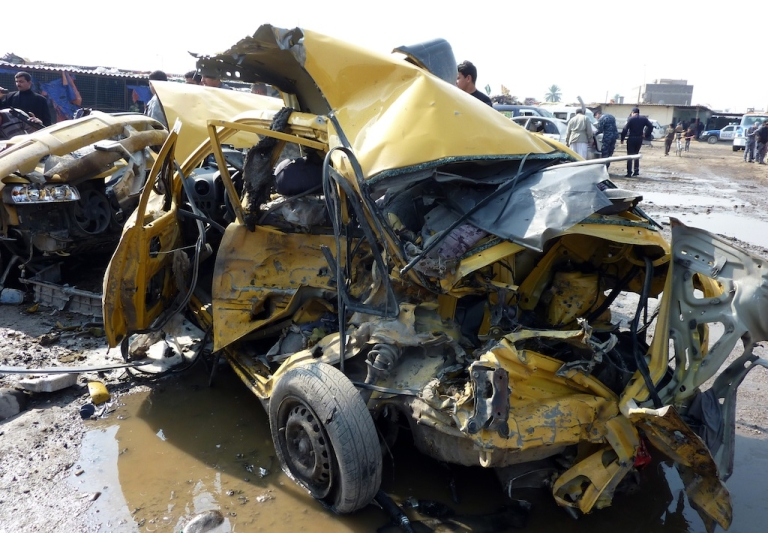 <p>A destroyed car lies at the scene of an explosion at the bird market in the north Baghdad Shiite neighbourhood of Kadhimiyah on Feb. 8, 2013.</p>