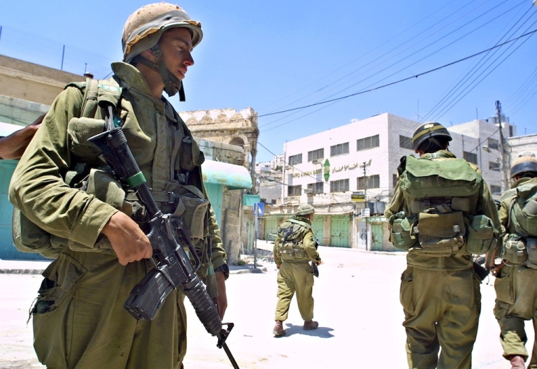 <p>Israeli soldiers patrol the empty streets of Hebron on June 26, 2002, in the West Bank.</p>