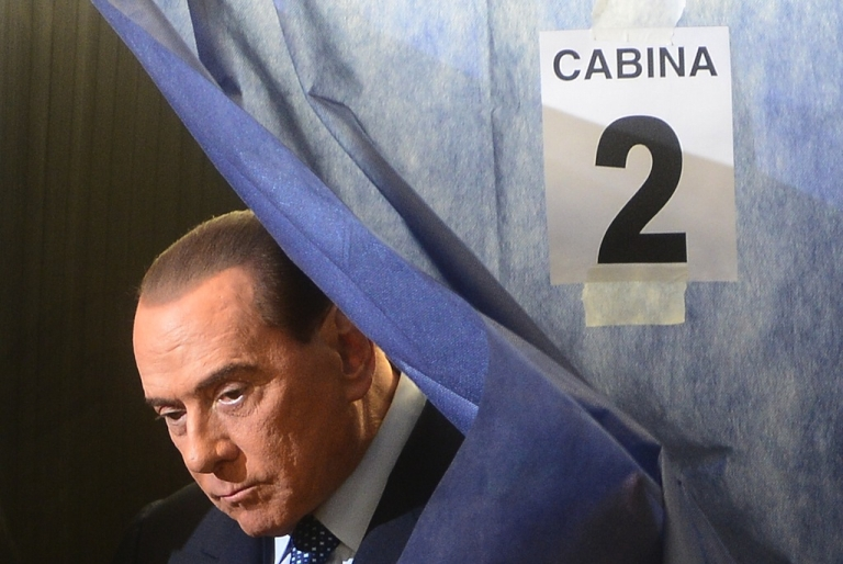<p>Italian former Prime Minister Silvio Berlusconi exists a voting booth at a polling station on Feb. 24, 2013 in Milan.</p>