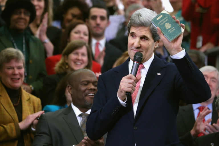 <p>US Secretary of State John Kerry holds up his first diplomatic passport he received as an 11-year-old boy while making remarks to employees on his first day at the State Department on Feb. 4, 2013, in Washington, DC.</p>