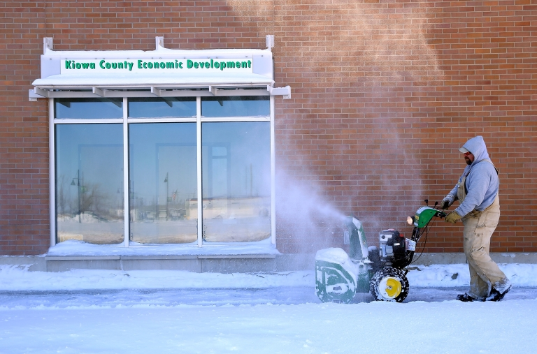 <p>A worker uses a snowblower to clear a path after a large winter storm on Feb. 22, 2013, in Greensburg, Kan.</p>