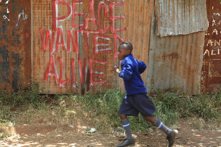 <p>A schoolboy runs past a message urging for peaceful polls on Monday.</p>