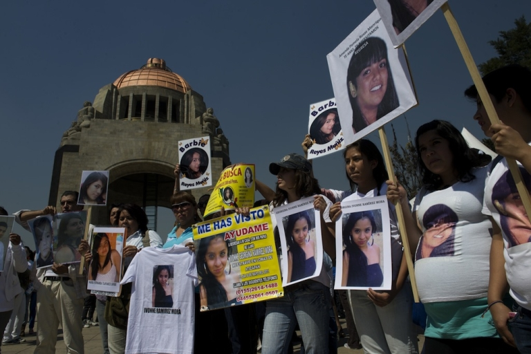 <p>People show pictures of missing women during Mexico's 'One Billion Rising' flashmob against violence against women, at the Republic Square in front of the Monument to the Mexican Revolution, in Mexico City on Feb. 14, 2013.</p>