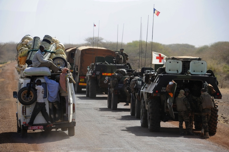 <p>A local truck passes a convoy of French army vehicles heading toward Gao on February 7.</p>