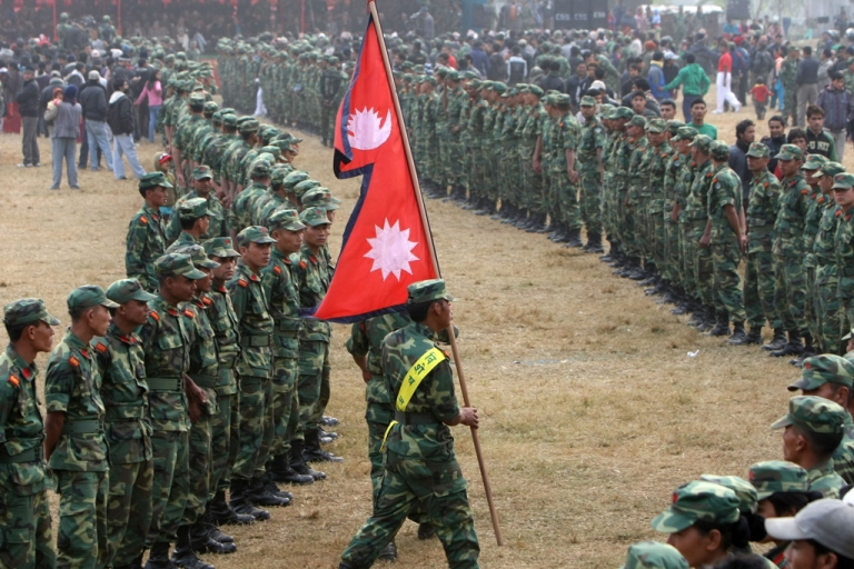<p>A former Nepali Maoist combatant holds the Nepalese flag as he marches during a special function at the Shaktikhor cantonment site in the Chitwan District of Nepal, some 170 km south of Kathmandu, on Jan. 22, 2011.</p>
