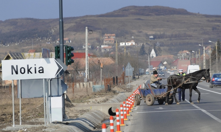 <p>A Romanian man maneuvers on his horse-drawn cart on a road with a sign pointing toward the Nokia factory in the village of Jucu, where the Finnish cellphone maker opened an assembly line plant.</p>