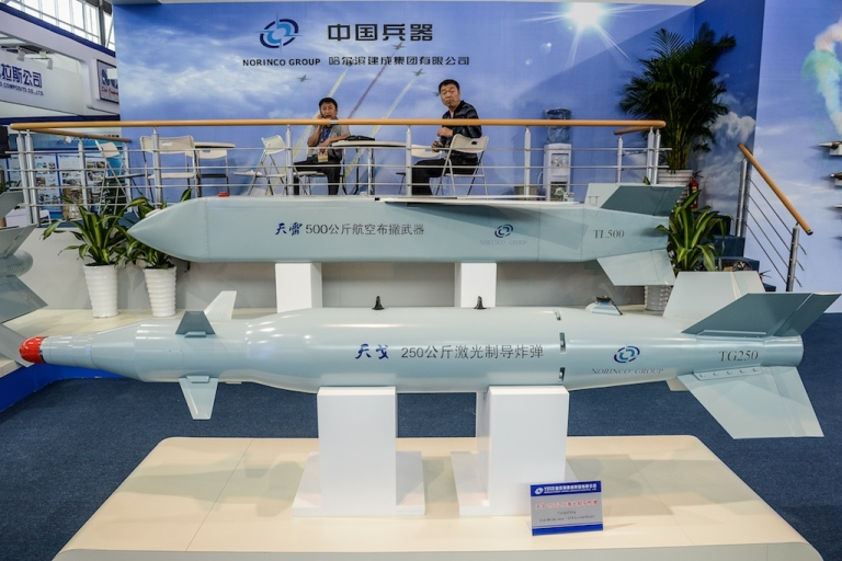 <p>Men sit by a display of missiles models from Chinese manufacturer Norinco Group on the eve of the ninth China International Aviation and Aerospace Exhibition in Zhuhai on Nov. 12, 2012.</p>