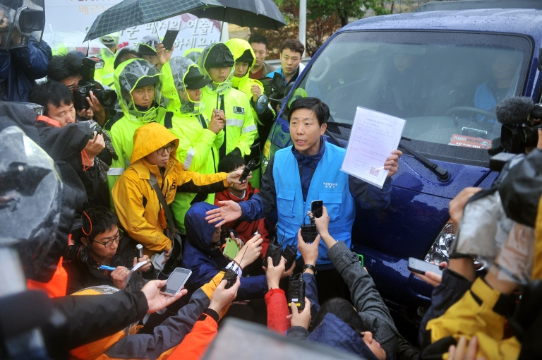 <p>Park Sang-Hak (C), an activist and former defector from North Korea, complains with a state document approving his planned rally near the border as policemen block his truck containing anti-North Korea leaflets on a roadway in Paju, north of Seoul, on October 22, 2012.</p>