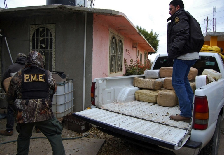 <p>Police unload packages of confiscated marijuana in Nuevo Laredo on January 8, 2010.</p>