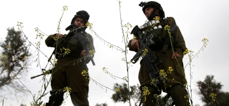 <p>Israeli soldiers stand guard during the weekly demonstration against Israel's controversial separation barrier in the village of Bilin, near the West Bank city of Ramallah.</p>