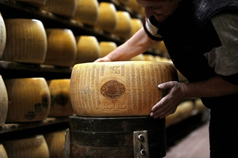 <p>A worker checking a wheel of seasoned Parmigiano Reggiano cheese in a factory in Valestra.</p>