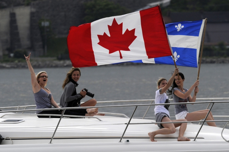 <p>Boaters wave Quebec and Canadian flags as they pass England's Prince William and wife Catherine, Duchess of Cambridge, in Quebec City on July 3, 2011.</p>