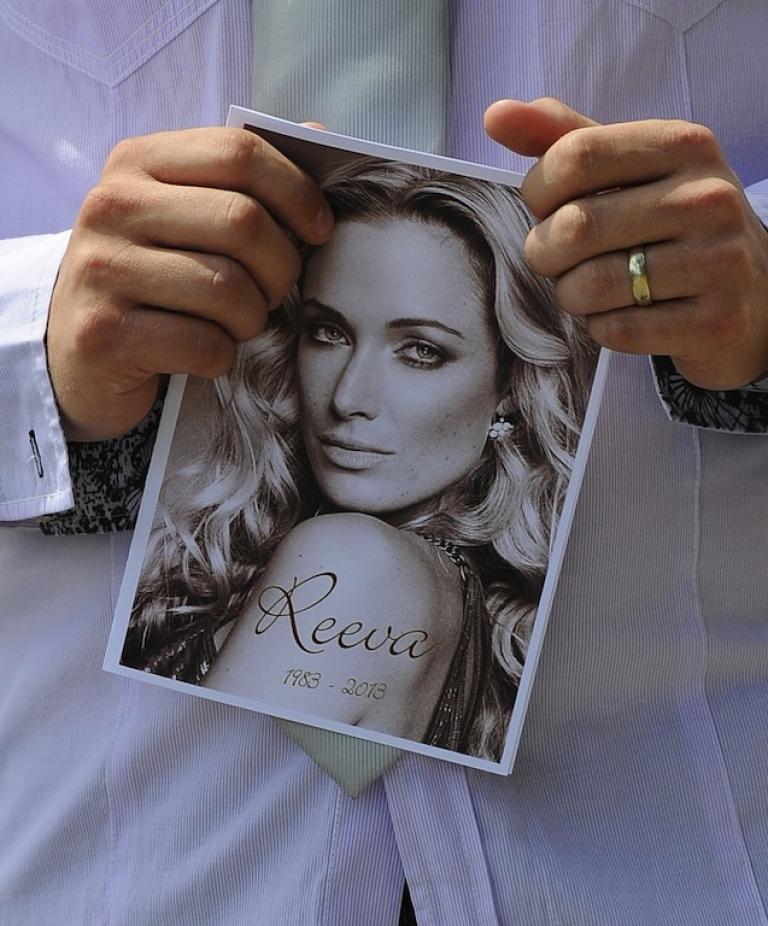 <p>A mourner holds a copy of the order of service for Reeva Steenkamp's funeral.</p>