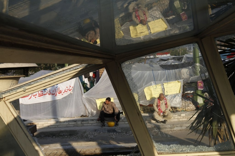 <p>Anti-government protesters sit in front of their plastic sheeting tents early morning in Tahrir Square on February 8, 2011, on the 15th day of protests calling for an end to President Hosni Mubarak's regime.</p>
