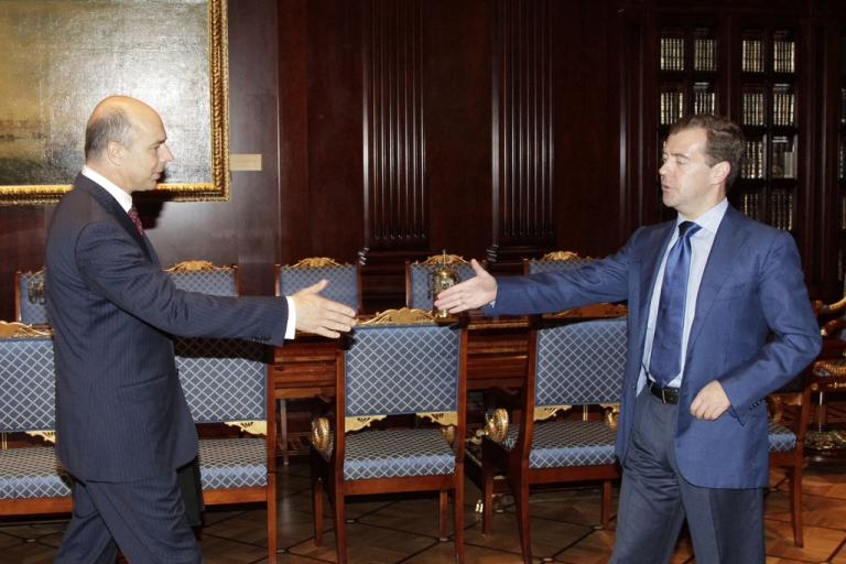 <p>Russia's former President Dmitry Medvedev (R) welcomes acting Finance Minister Anton Siluanov (L) during a meeting on Sept. 28, 2011. Siluanov made headlines recently for his criticism of countries that are trying to stimulate their economies through currency devaluation.</p>