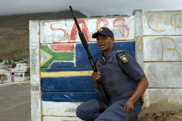 <p>A member of the South African Police Services (SAPS) takes cover behind a wall from rocks being thrown by protesters during a farm worker strike on January 14, 2012 in Villiersdorp, a small farming town about 100 km borth of Cape Town, South Africa. A new report has found that nearly 1,500 South African police officers have criminal records.</p>