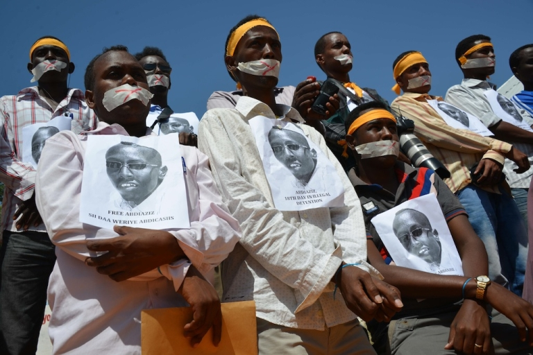 <p>Somali journalists simulate being handcuffed and hold up pictures of their arrested colleague, Abdiaziz Abdinor Ibrahim, condemning his long term in jail on January, 27, 2013 in Mogadishu.</p>
