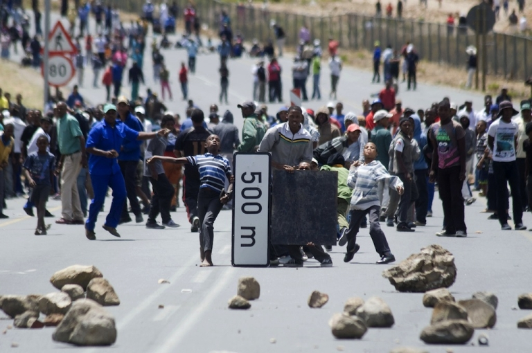 <p>Striking farm workers and other protestors throw stones, while hiding behind broken road signs during violent clashes with members of the South African Police Services (not visible), on January 10, 2013 in de Doorns, a small farming town about 140 km North of Cape Town, South Africa. The farm workers have said that they they will not return to work on the fruit growing region's farms until they receive a daily wage of at least R150 ($17) per day, which is about double what they currently earn.</p>