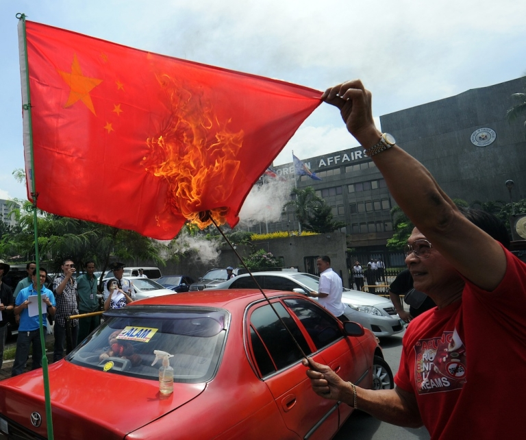 <p>A Filipino activist burns a Chinese flag during a protest in Manila on July 27, 2012, amidst the heightening tension between the Philippines and China over the disputed South China Sea.</p>