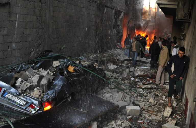 <p>Syrian men inspect the scene of a car bomb explosion in Jaramana, a mainly Christian and Druze suburb of Damascus, on Nov. 28, 2012.</p>