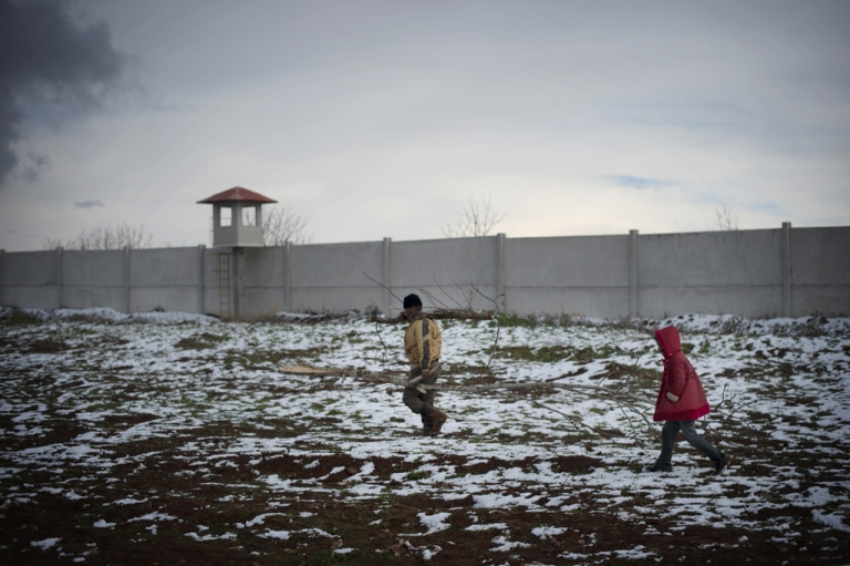 <p>A Syrian refugee child helps a man to collect wood at a refugee camp in Bab al-Salam on the Syria-Turkey border, on January 9, 2013.</p>