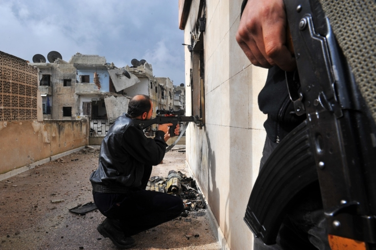 <p>A rebel fighter shoots towards Syrian government forces through a window at a flat in the Salaheddine neighborhood of Aleppo on February 16, 2013. A new UN report says both rebels and government forces are responsible for war crimes during the ongoing conflict.</p>